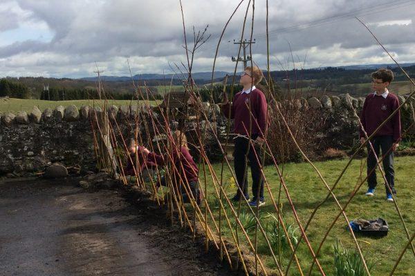 School children building structure to grow plants
